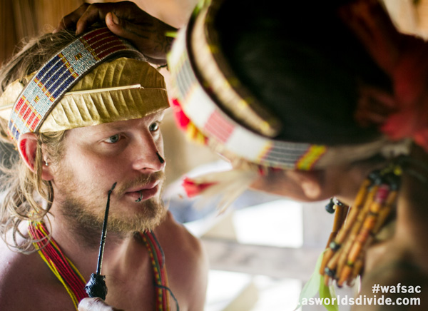 Australian tourist receiving custom face paint from Mentawai Sikerei during ceremony